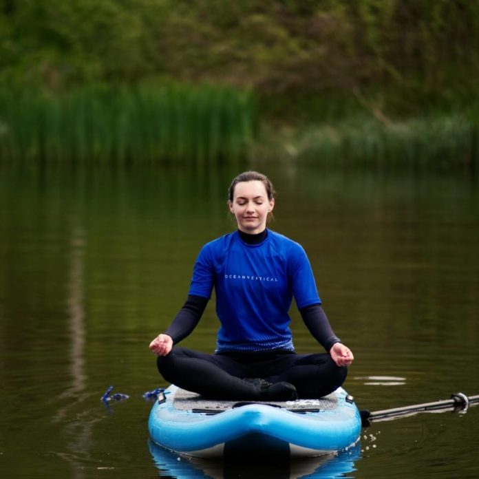 SUP yoga on a paddle board mindfulness and peace with ocean vertical in east lothian